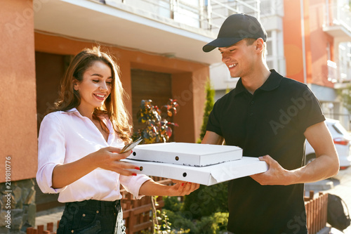 Fotografía  Pizza Delivery. Courier Giving Woman Boxes With Food Outdoors