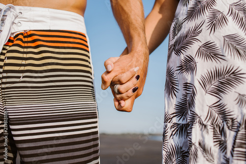Fototapety, obrazy: cropped image of couple holding hands on beach in bali, indonesia