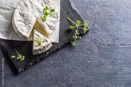 Cheese camambert from oregano herbs on slate board