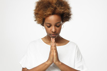 Closeup Of Young African American Woman Isolated On Gray Background Putting Hands Together As If She Is Praying With Closed Eyes To Overcome Depression