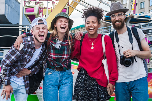 Poster Attraction parc happy young multiethnic friends standing together and laughing in amusement park