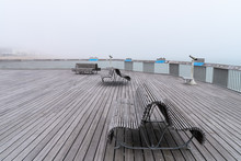 The Pier Of Hastings On A Misty Summer Day With Benches And Telescopes, No People, Sea And Buildings In The Distance