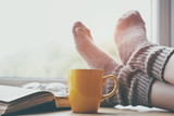 Woman resting keeping legs in warm socks on table with morning coffee and reading book