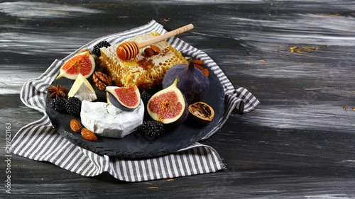 Camembert cheese with honey, figs, walnuts on stone board on a dark background, Flat lay, Copy space