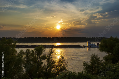 Fotografia  A towboat with barges in the Mississippi river at sunset near the city of Vicksburg in the State of Mississippi, USA