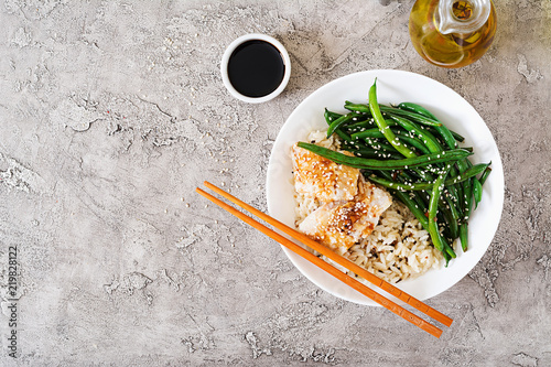 Fish fillet served with rice, soy sauce and green beans in white plate. Asian food. Top view. Flat lay