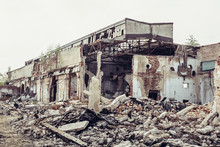 Ruined Abandoned Industrial Building With Large Pills Of Concrete Garbage, Aftermath Of Natural Disaster, Hurricane, Earthquake Or War
