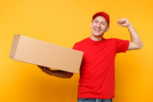Delivery Man In Red Uniform Isolated On Yellow Orange Background. Professional Male Employee Courier Or Dealer In Cap T-shirt Holding Empty Cardboard Box. Receiving Package Service Concept. Copy Space