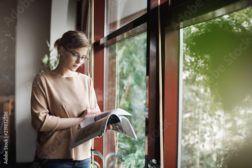 7a0ed34b9e Woman likes spend time with reading. Indoor shot of cute creative and smart  female in trendy outfit and glasses