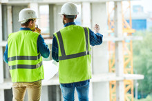 Back View Portrait Of Two Construction Workers Wearing Hardhats And Reflective Vests Discussing Engineering Plans On Site, Copy Space