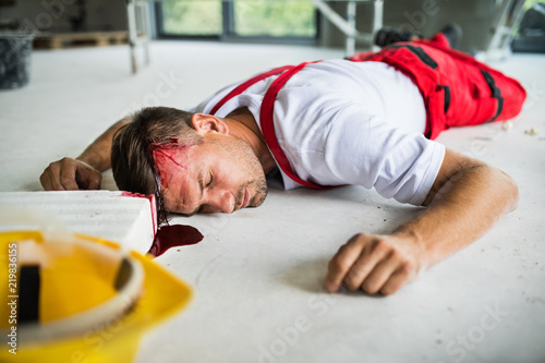 An unconscious man worker lying on the floor after accident on the construction site Canvas Print