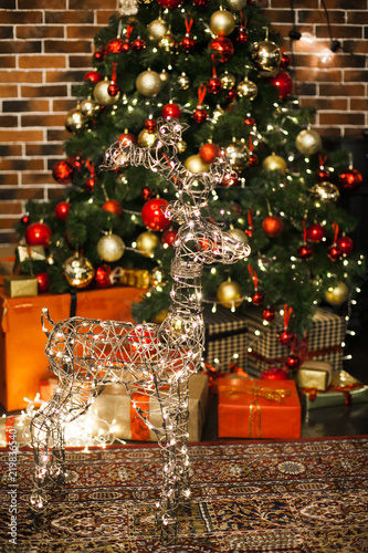 Beautiful Christmas deer with the glowing lights at night in living room with decorated Christmas tree, gifts. New Year loft interior with New year tree with red and gold decor balls