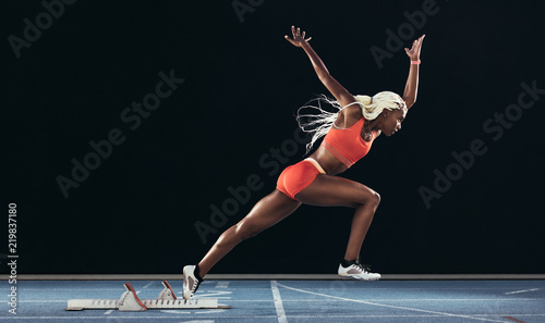 Fotomural Woman athlete taking off from starting block on a running track