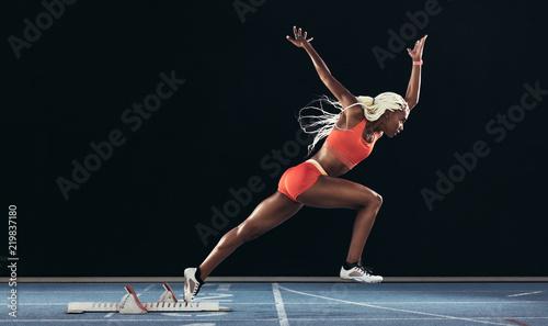 Carta da parati Woman athlete taking off from starting block on a running track