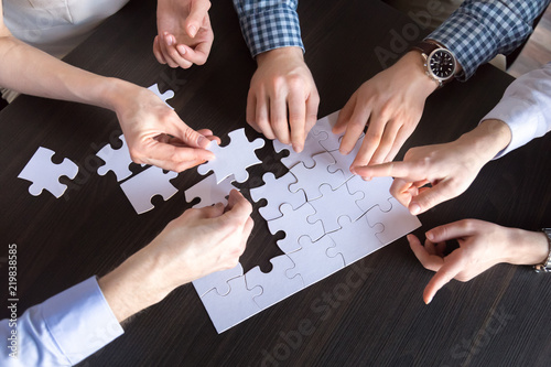 Top close up view of diverse employees assembling jigsaw puzzle trying to find best business solution, workers engaged in teambuilding practicing unity and support Canvas Print