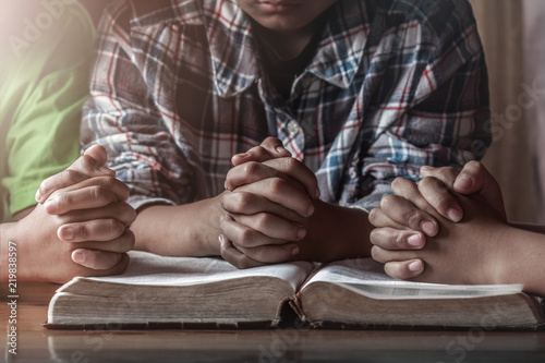 christian children group praying on wooden table with open bible, prayer meeting Fotobehang