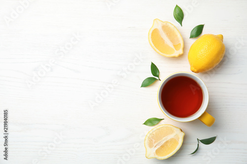 Fotobehang Thee Cup of black tea and lemons on wooden table, top view