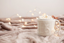 Hot Chocolate With Marshmallows On Soft Plaid Background With Christmas Lights. Perfect Winter Time Treat.