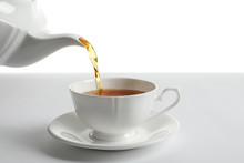 Pouring Hot Tea Into Porcelain Cup On White Background