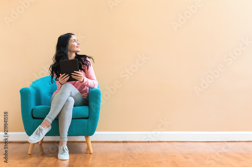 Young woman using her tablet on a blue chair