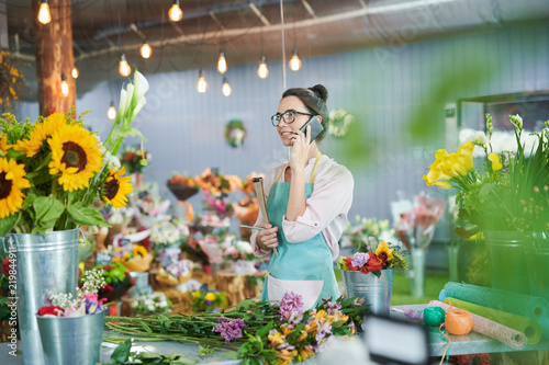 Side view portrait of young woman speaking by phone in flower shop
