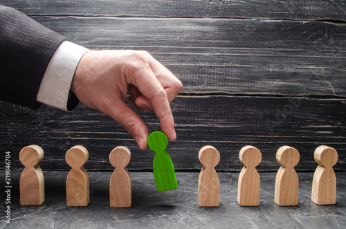 Fotografiet  hand of a businessman takes a wooden figure of a man