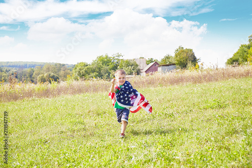Photo  Little boy with the flag of the United States of America.