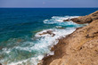 Blue sea waves on a rocky beach, Crete, Greece. Mediterranean coast. Travel and vacation on the beach. Beautiful seascape..