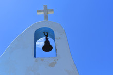 A Cross And A Bell On A Greek Orthodox Church In Peloponnese
