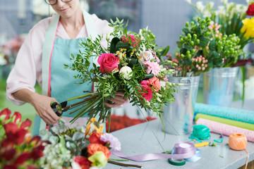 Izrežite pogled nasmiješene žene koja u butiću dogovara buket cvijeća
