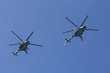 Several Military Helicopters Fly Side By Side Against The Blue Sky