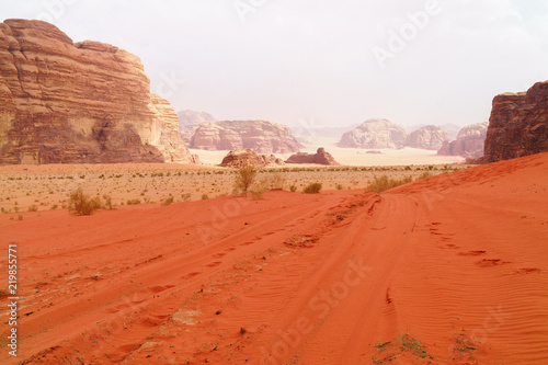 Wadi Rum desert, Jordan, Middle East, known as The Valley of the Moon. Orange sand, blue sky, haze and clouds. Designation as a UNESCO World Heritage Site. Red planet Mars landscape.