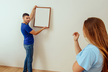 Man Hanging Blank Picture Fram...