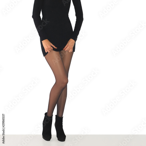 Fényképezés  Long slim female legs in black tights and fitting dress isolated on white