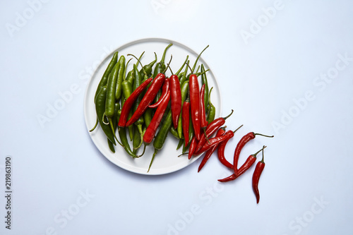 Flat lay of hot chili pepper green and red in a white plate on a white background Wallpaper Mural