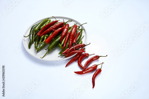 Photo  Hot chili pepper green and red in a white plate on a white background