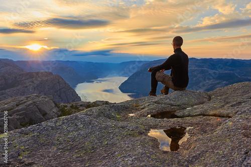 Valokuva  Mann sitzt auf dem Berggipfel nach vollendeter Wanderung mit Blick in Richtung S