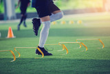 Fototapeta Sport - Kid soccer player Jogging and jump between marker and yellow hurdles. Soccer training.