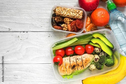 school lunch boxes with chicken, avocado, eggs and fresh vegetables, bottle of water, nuts and fruits