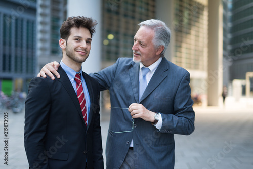 Obraz Portrait of a confident senior businessman talking to a younger colleague - fototapety do salonu