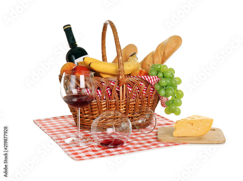 Picnic basket with food and glasses of wine on white background