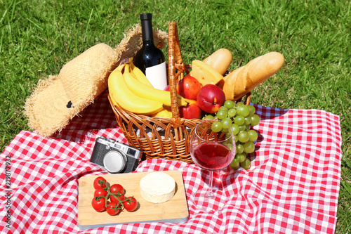 Basket with food and glass of wine on blanket prepared for picnic in park