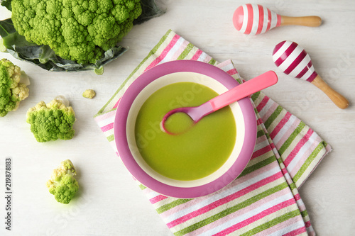 Flat lay composition with plate of healthy baby food on light background