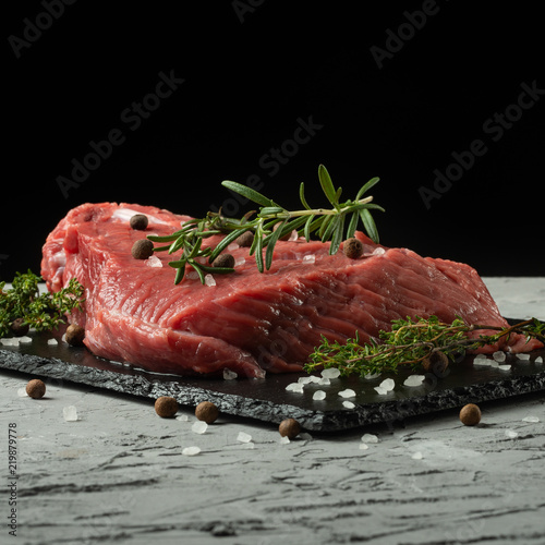 Papiers peints Steakhouse Raw fillet of beef steak with rosemary, thyme, and spices on a blackboard.