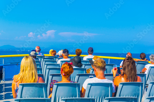 Fotografia Tourists sitting on an upper deck of a ferry travelling from Saint Tropez to Sai