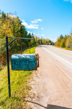 Weathered Rural Mailbox Hanging From Chains & Metal Post At Roadside On An Bright Sunny Autumn Day. Long View With Copy Space