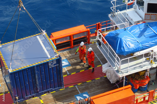 Supply boat transfer cargo to oil and gas industry and moving cargo from the boat to the platform. Boat is waiting transfer cargo and crews to platform.
