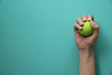 Woman Holding Stress Ball On Green Background