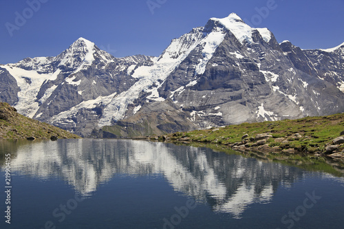 Poster Reflexion Summer in the Swiss Alps, Murren area, overlooking the Monch and Jungfrau mountains reflected in Grauseewli Lake, Canton of Bern, Switzerland, Europe
