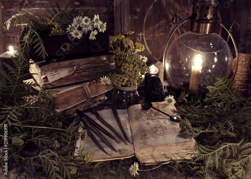 Old books, antique lamp, black candles and witch herbs. Mystic background with ritual esoteric objects, occult, fortune telling and halloween concept